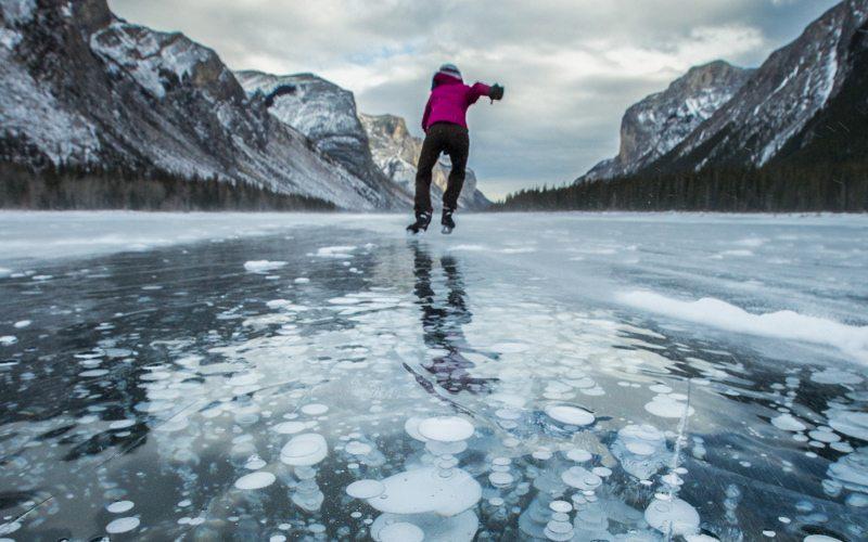 Ice skating on Lake Minnewanka is a spectacular early winter adventure. Photo: Paul Zizka.