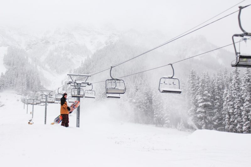 Snowboarder by chair lift at Mt. Norquay, Banff National Park.
