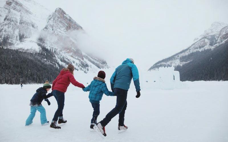 Family ice skating at Lake Louise, Banff National Park.