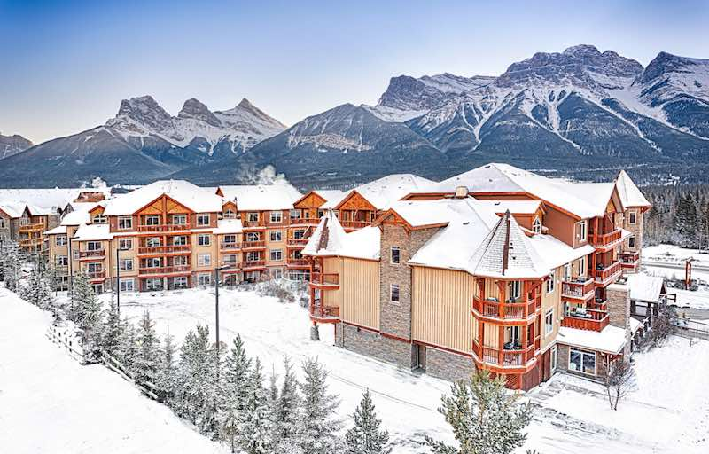 Falcon Crest Lodge in winter, with mountains in background, Canmore, Alberta.