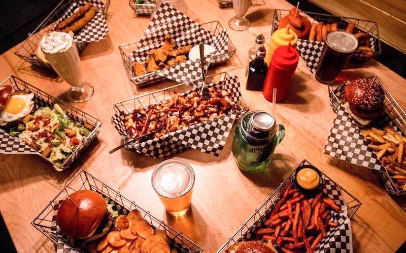 Burger and beverage spread at Eddie Burger + Bar in Banff, Alberta.
