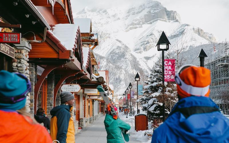 Skiers walk down Banff Avenue with their gear in winter.