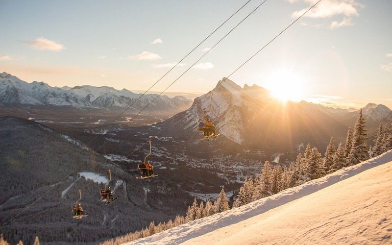 Skiers on the North American Chair at Mt. Norquay, with Mount Rundle and town of Banff.