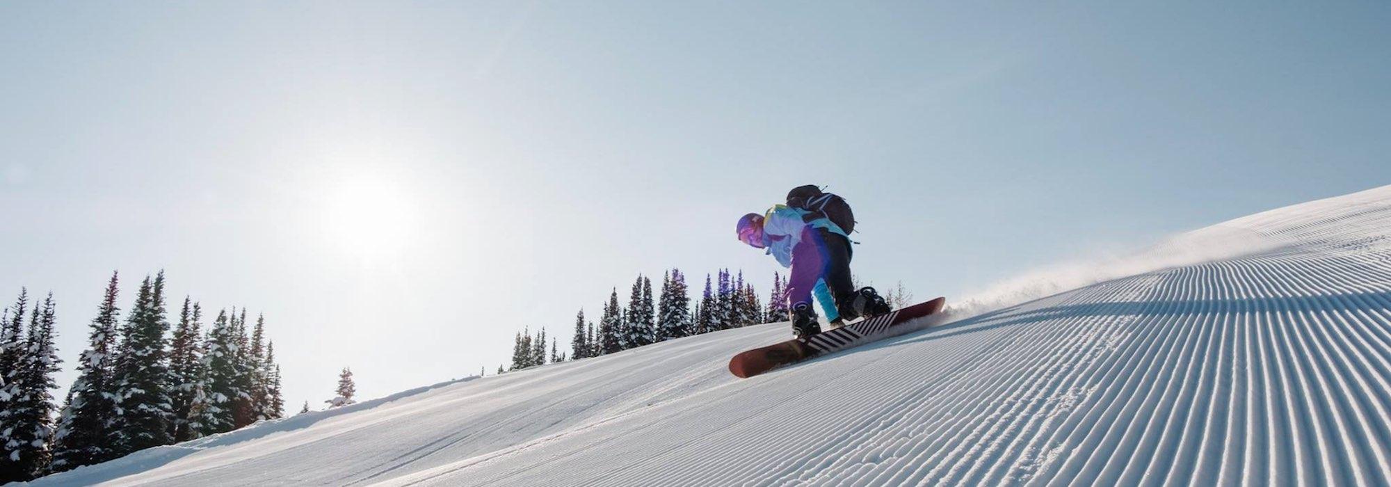 Snowboarder rides a corduroy run at Banff Sunshine Village ski resort, Banff National Park.