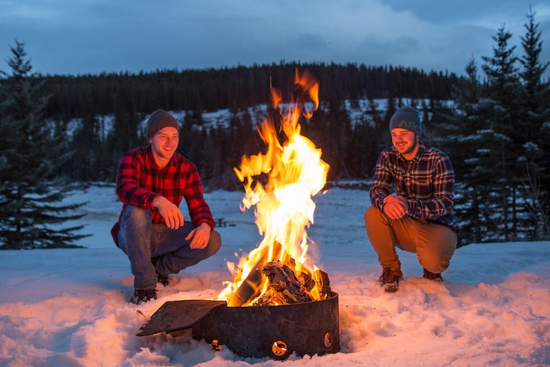 Two people crouch near an outdoor winter campfire at Cascade Ponds, Banff National Park. Photo by Taylor Burk.