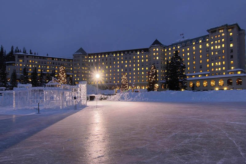 Night photo of frozen lake, ice castle, and Fairmont Chateau Lake Louise in Banff National Park.