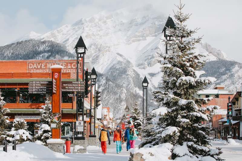 Group of skiers walks down Banff Avenue in winter with ski gear. Photo by Mike Seehagel.