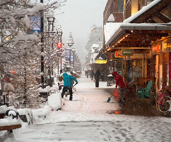 Person shoveling snow on Banff Ave, Banff National Park.