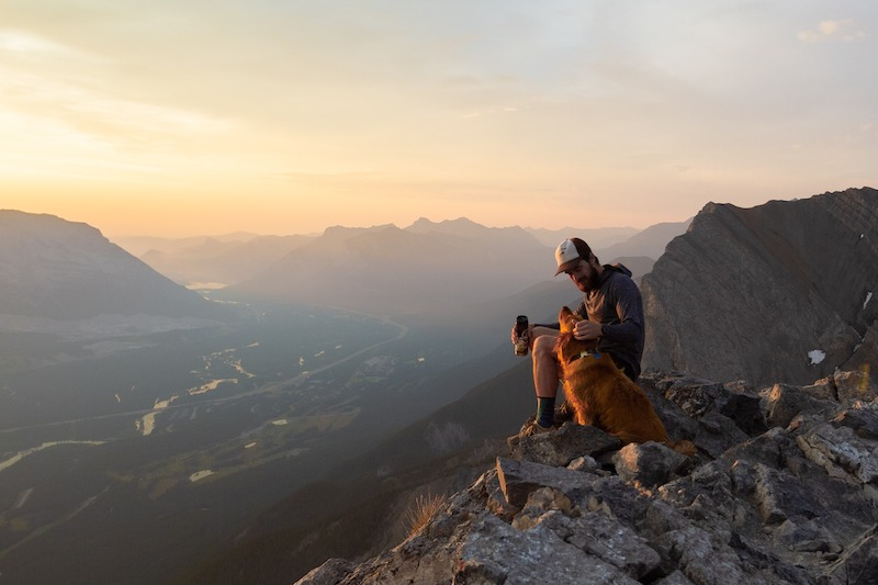 Hiker and dog on summit of Ha Ling at sunrise, near Canmore, Alberta.