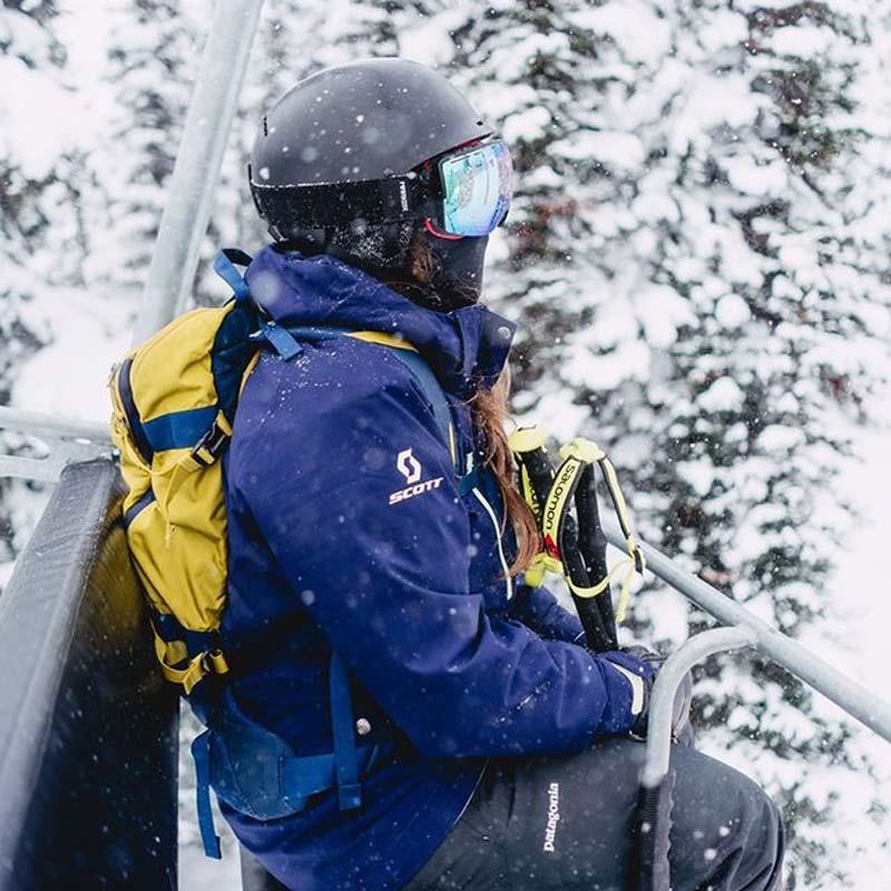 Femme portant un masque sur un télésiège au Banff Sunshine Village, dans le parc national de Banff.