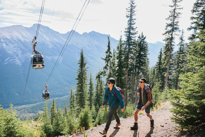 Two hikers on Sulphur Mountain trail in Banff National Park, Banff Gondola and Mount Rundle in background.