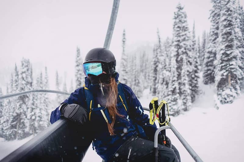 Woman wearing a mask on a chairlift at Banff Sunshine Village, Banff National Park.