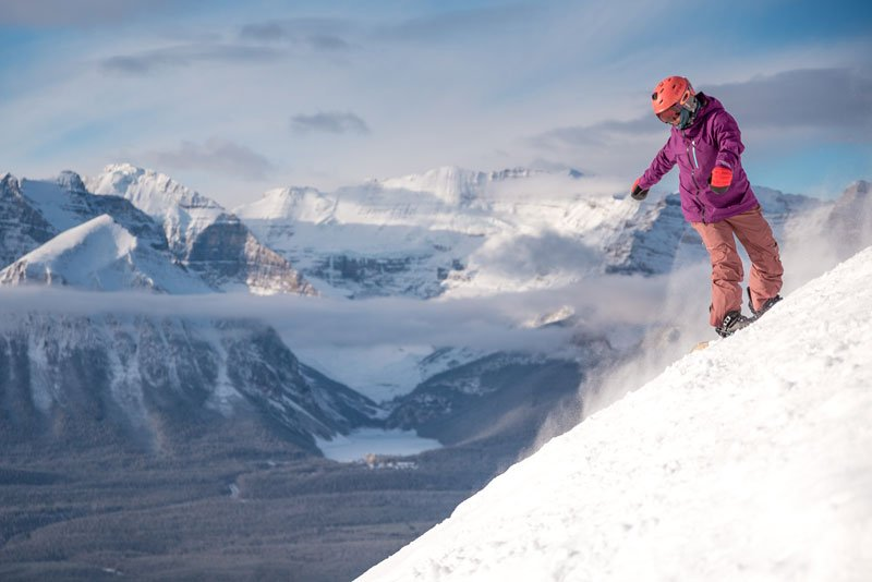 Snowboarder in scenic shots at Lake Louise Ski Resort with view of Mt. Temple and Lake Louise.
