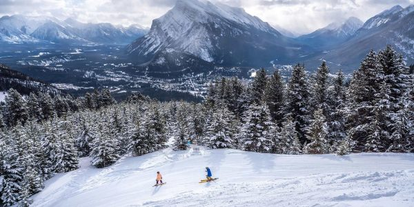 Skier And Snowboarder at Mt. Norquay ski resort, Mt. Rundle in the background. Banff National Park. Photo: John Price