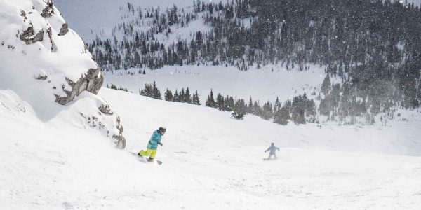 Two snowboarder kids in South Side Chutes at Banff Sunshine Village, Banff National Park. Photo by Travis Rousseau.
